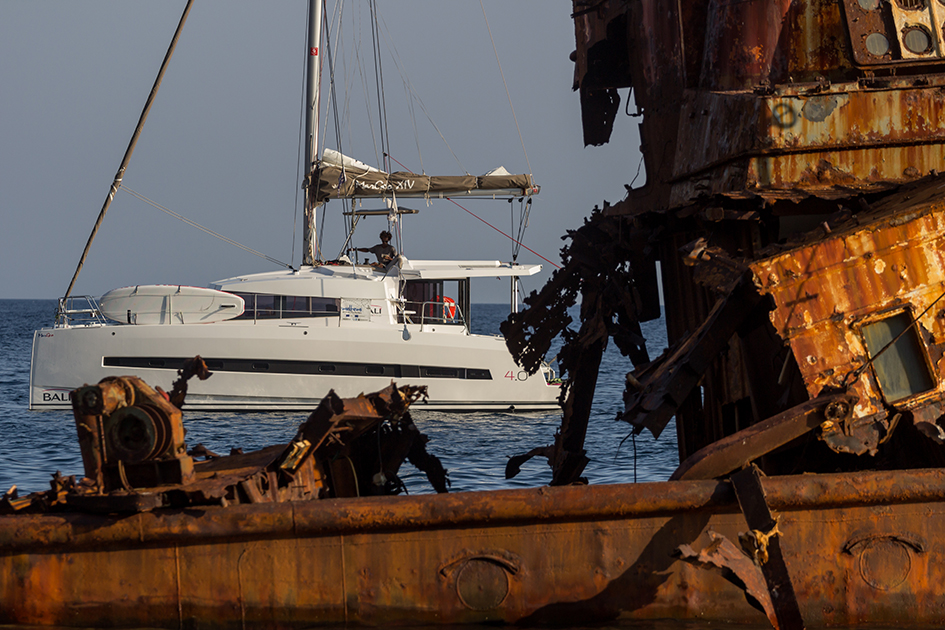 photo of an old wreck ship and a yacht in the background
